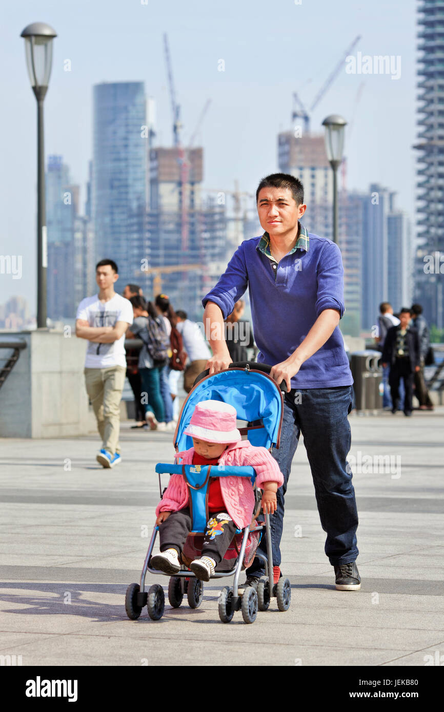 Young father with baby car. After 30 years of China's one child policy, many families won't take a second child - Stock Image