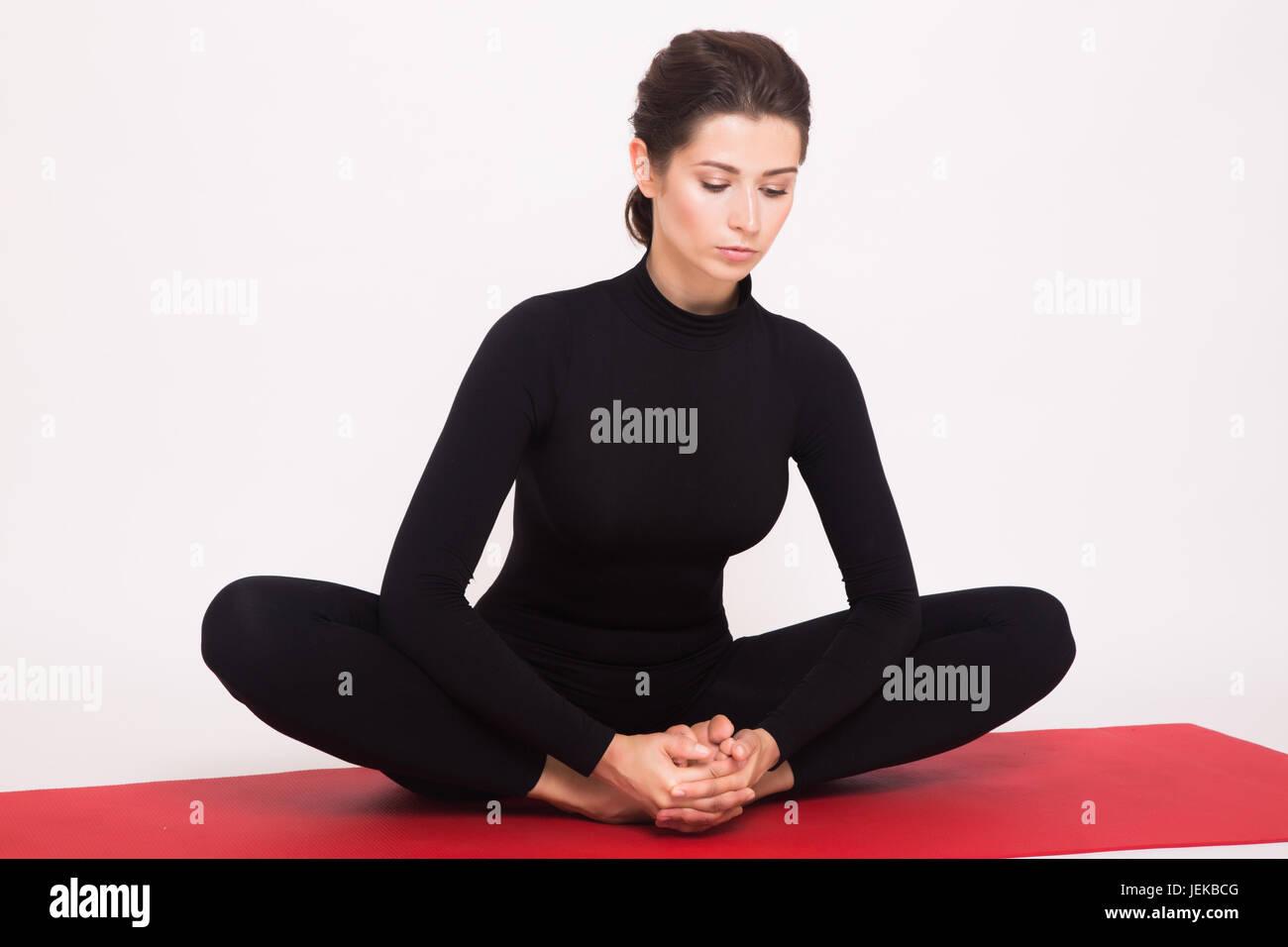 Beautiful athletic girl in black suit doing yoga asanas. Isolated on white background. - Stock Image