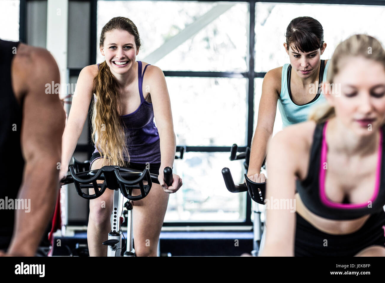 Fit women working out at spinning class - Stock Image