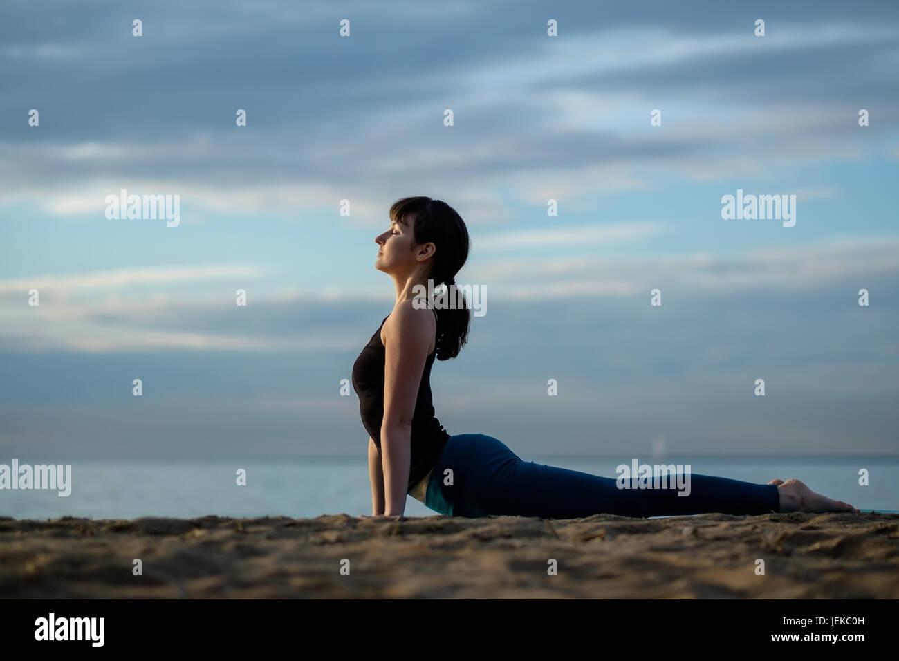 Yoga asana outdoors on beach. up facing dog pose - Stock Image