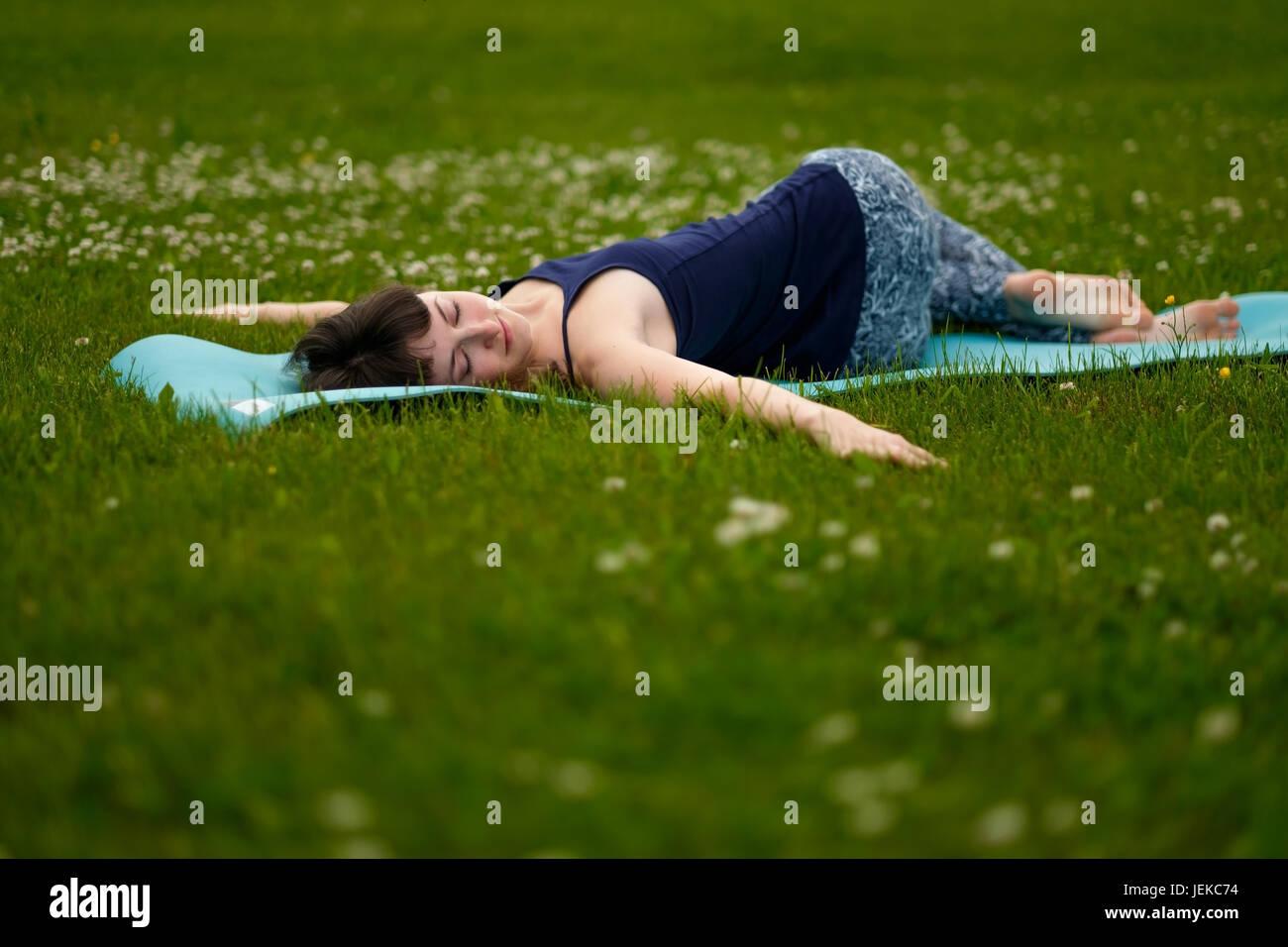 Beautiful caucaisan young woman working out outdoors on blue mat. Jathara Parivartanasana top view - Stock Image