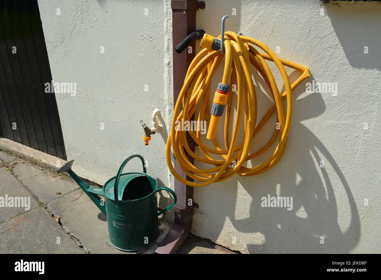Yellow garden hose pipe hanging off plastic coated metal hook outside of painted garage with green metal watering - Stock Image