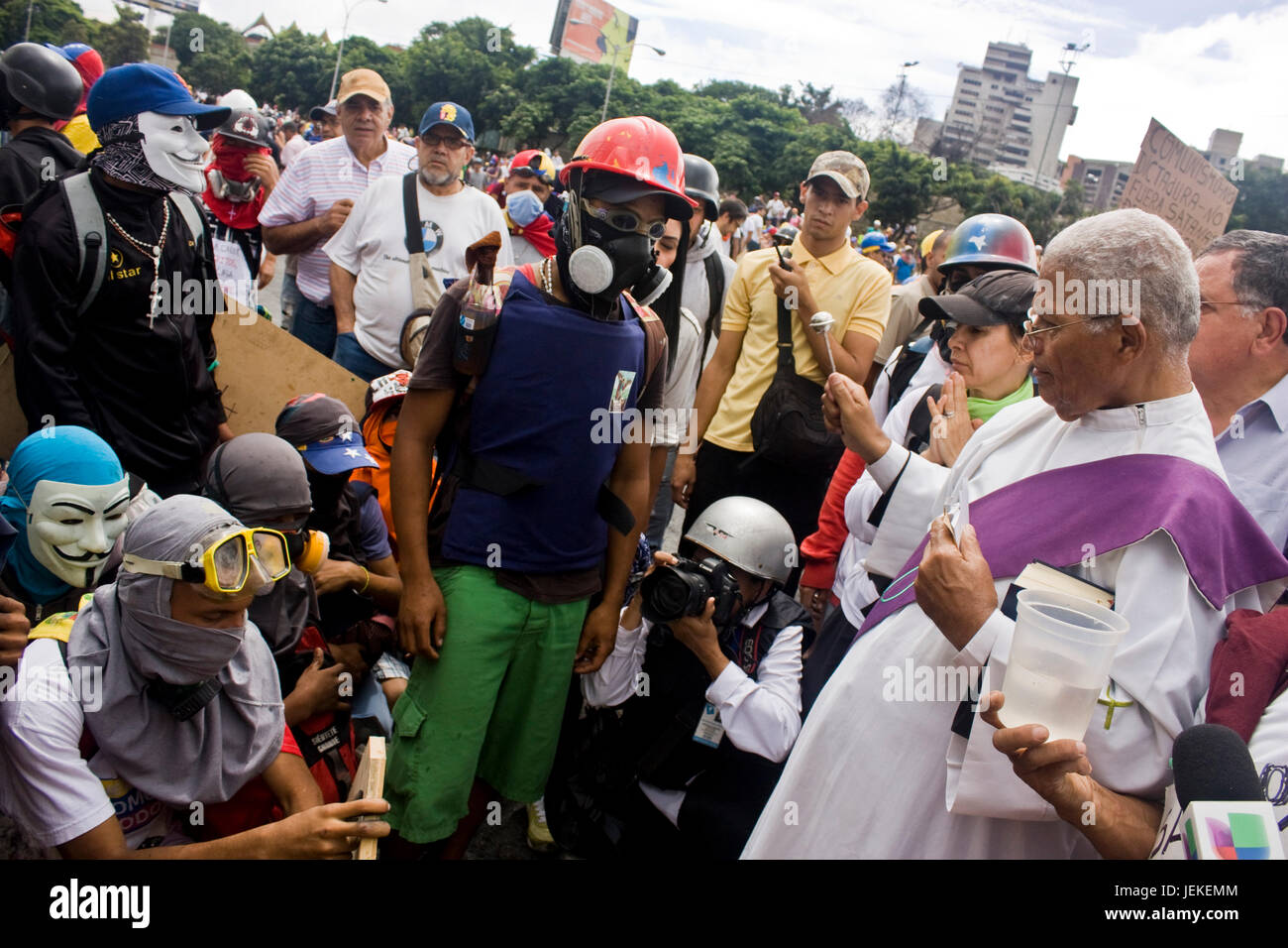A priest talks and bless a group of demonstrators outside of a military air base during a protest against president - Stock Image