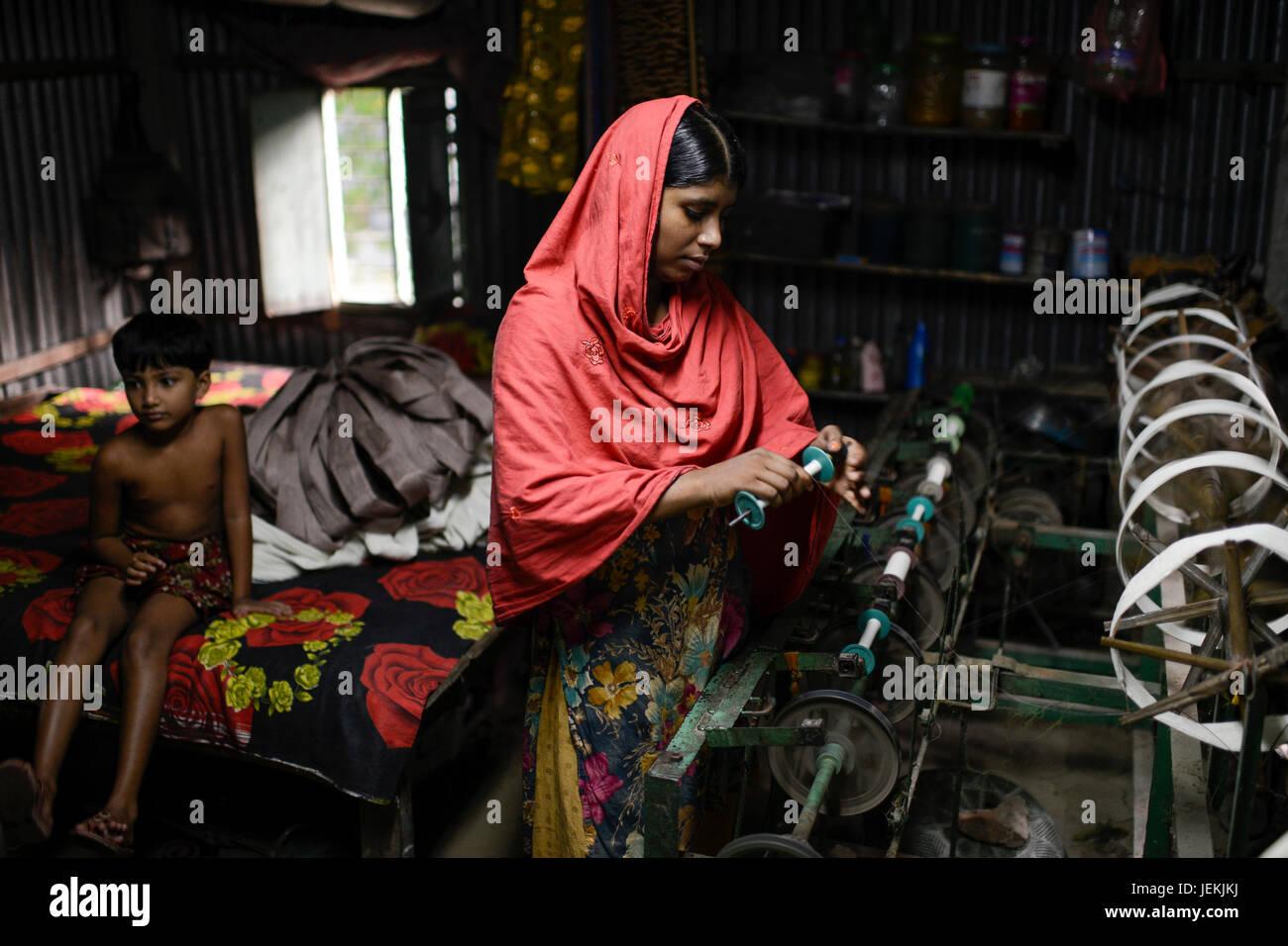 BANGLADESH, District Tangail, Kalihati, village Southpara, cottage industry, young woman working at spinning machine - Stock Image