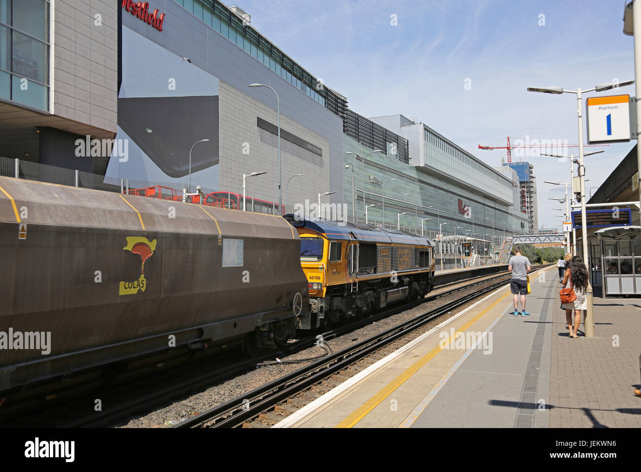 A goods train passes through the newly constructed Shepherds Bush station, next to the Westfield Shopping centre - Stock Image