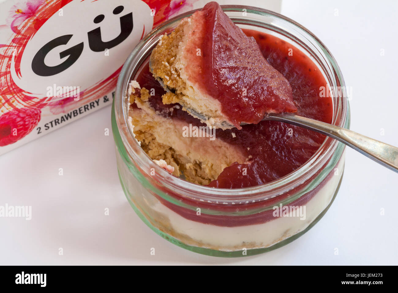 Gu strawberry & raspberry shortbread cheesecakes - ramekin removed from box and lid removed, with spoonful ready - Stock Image