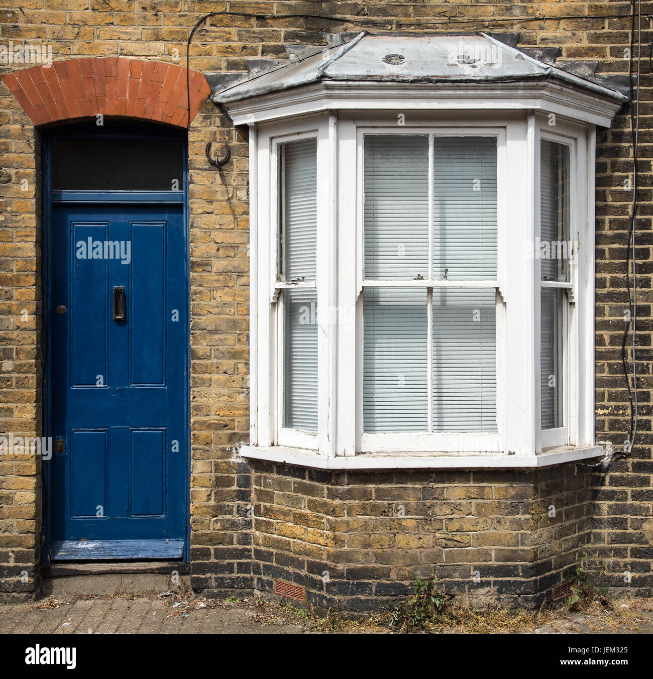 Traditional English house front entrance with blue closed doors and windows & Traditional English house front entrance with blue closed doors and ...