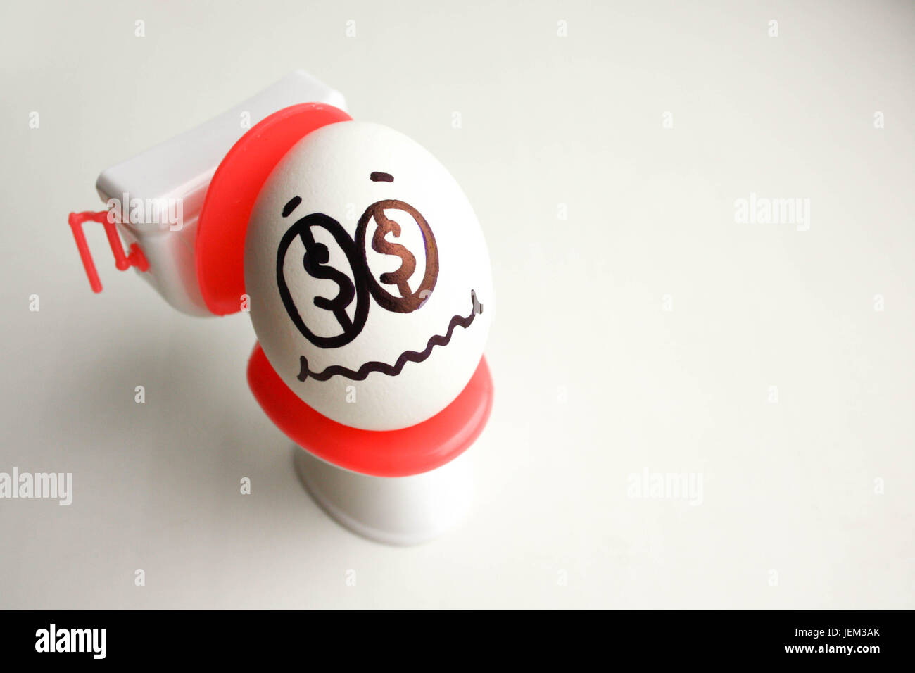 Concept of unprofitable business. An egg with a painted face on the toilet. Photo for your design - Stock Image