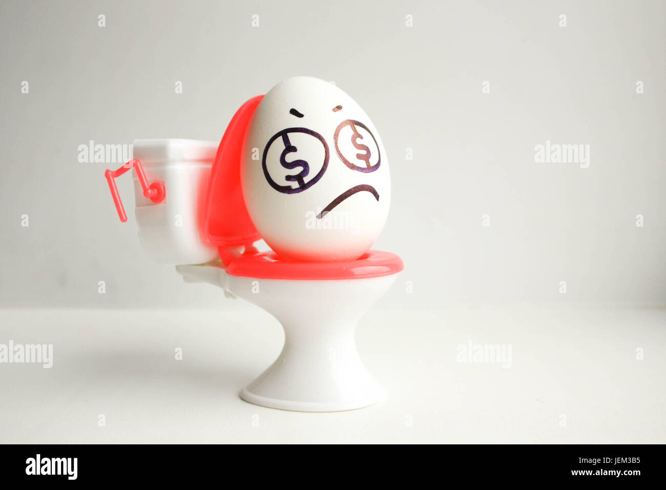 Concept of business unprofitable. An egg with a painted face on the toilet. Photo for your design - Stock Image