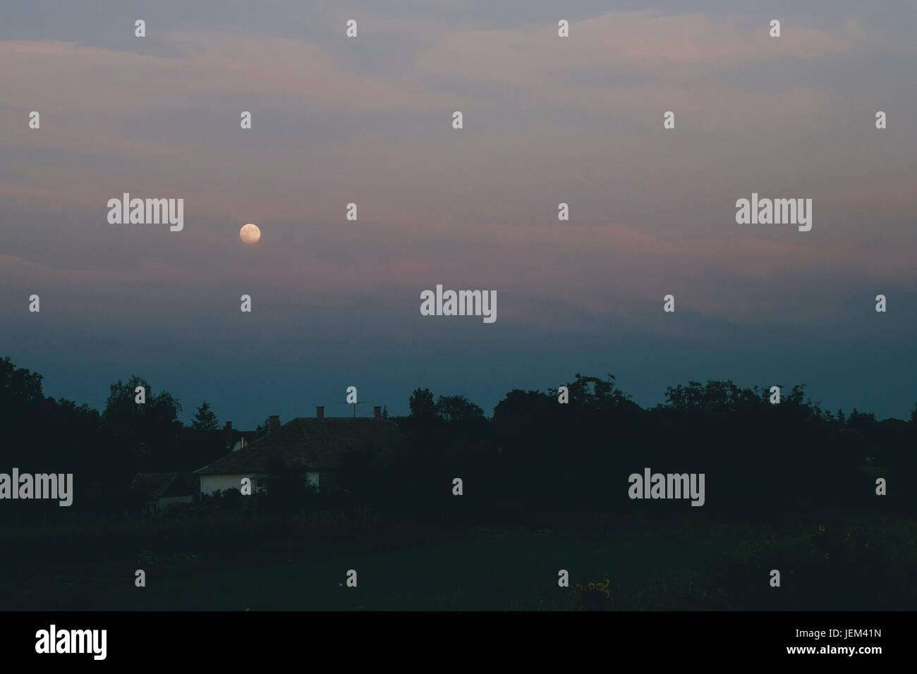 Moonrise over village - Stock Image