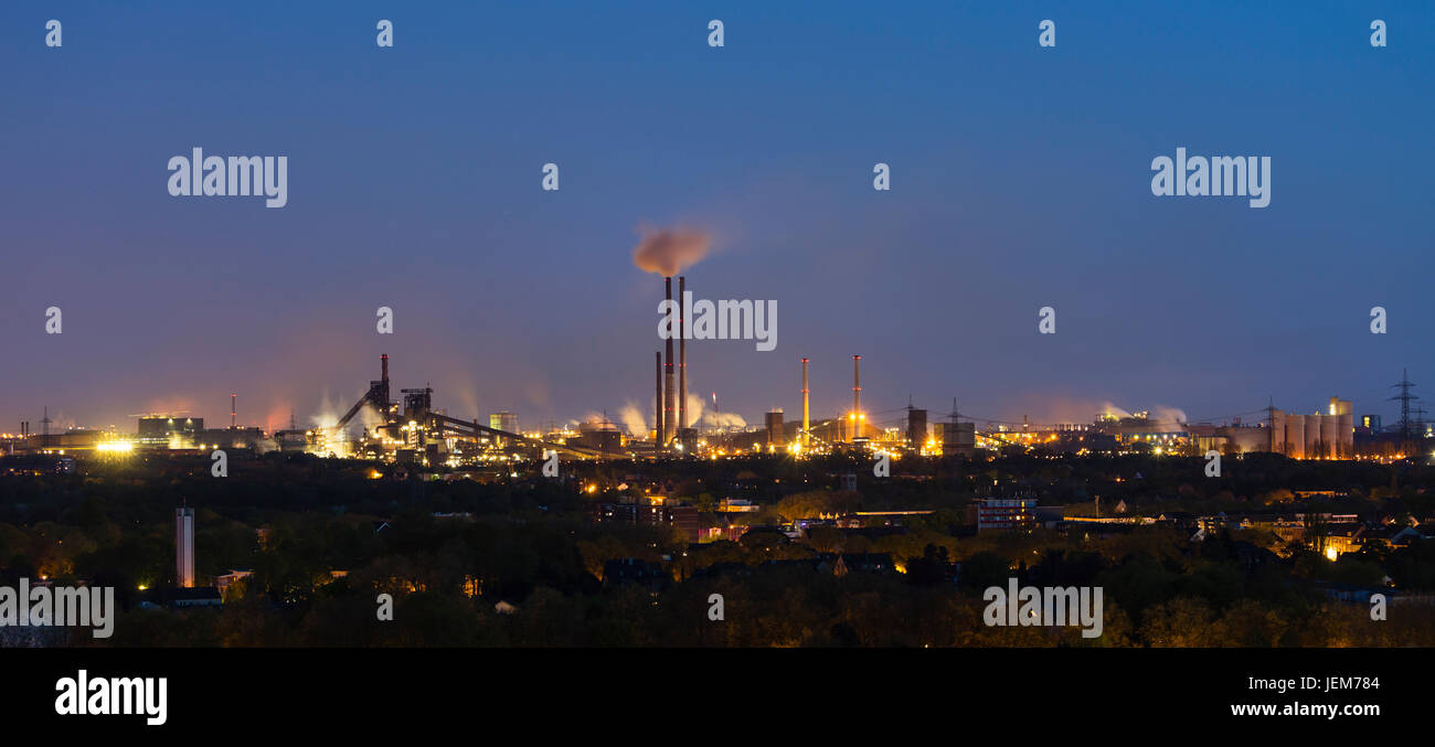 Panoramic view of a large coking and steel plant in Duisburg, Germany in the night with tapping resulting in the - Stock Image