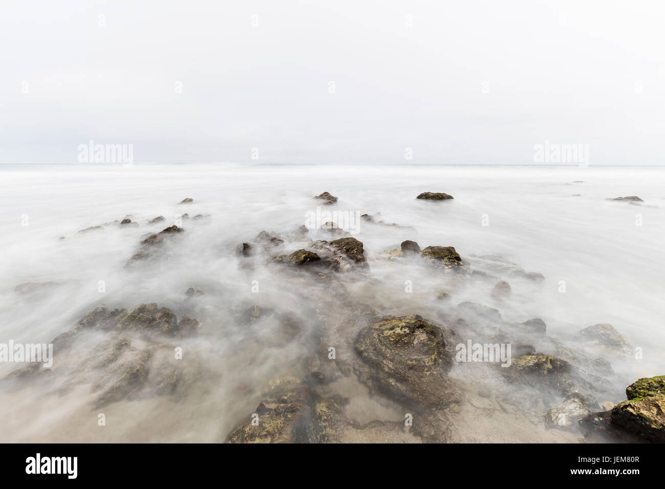 Foggy pacific ocean tidal pool with motion blur at Point Dume in Malibu California. - Stock Image