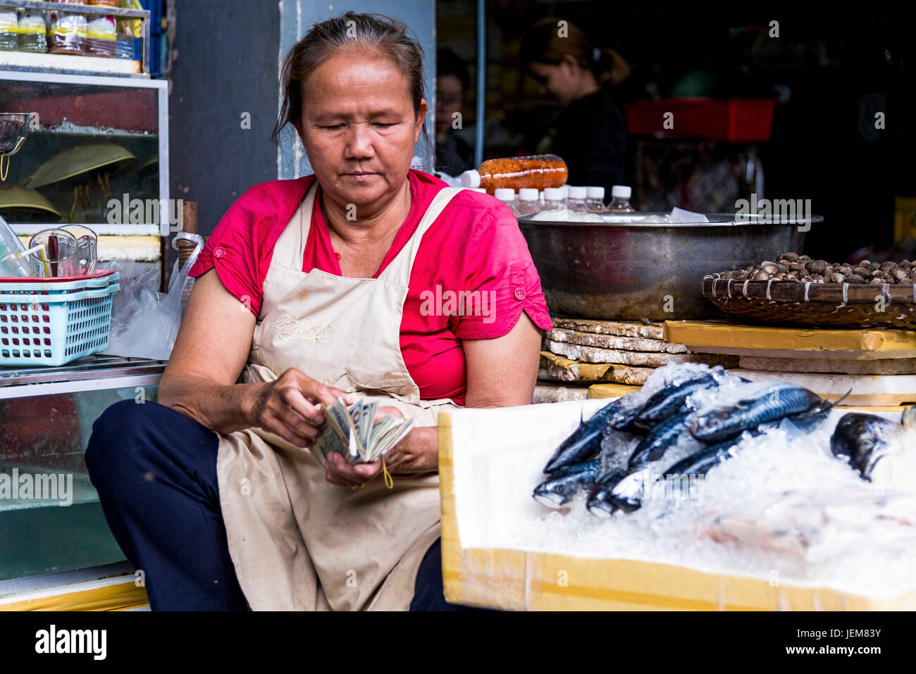 Phnom Penh, Cambodia - December 30, 2016: An unidentified woman check the day's earnings at the Central Market - Stock Image