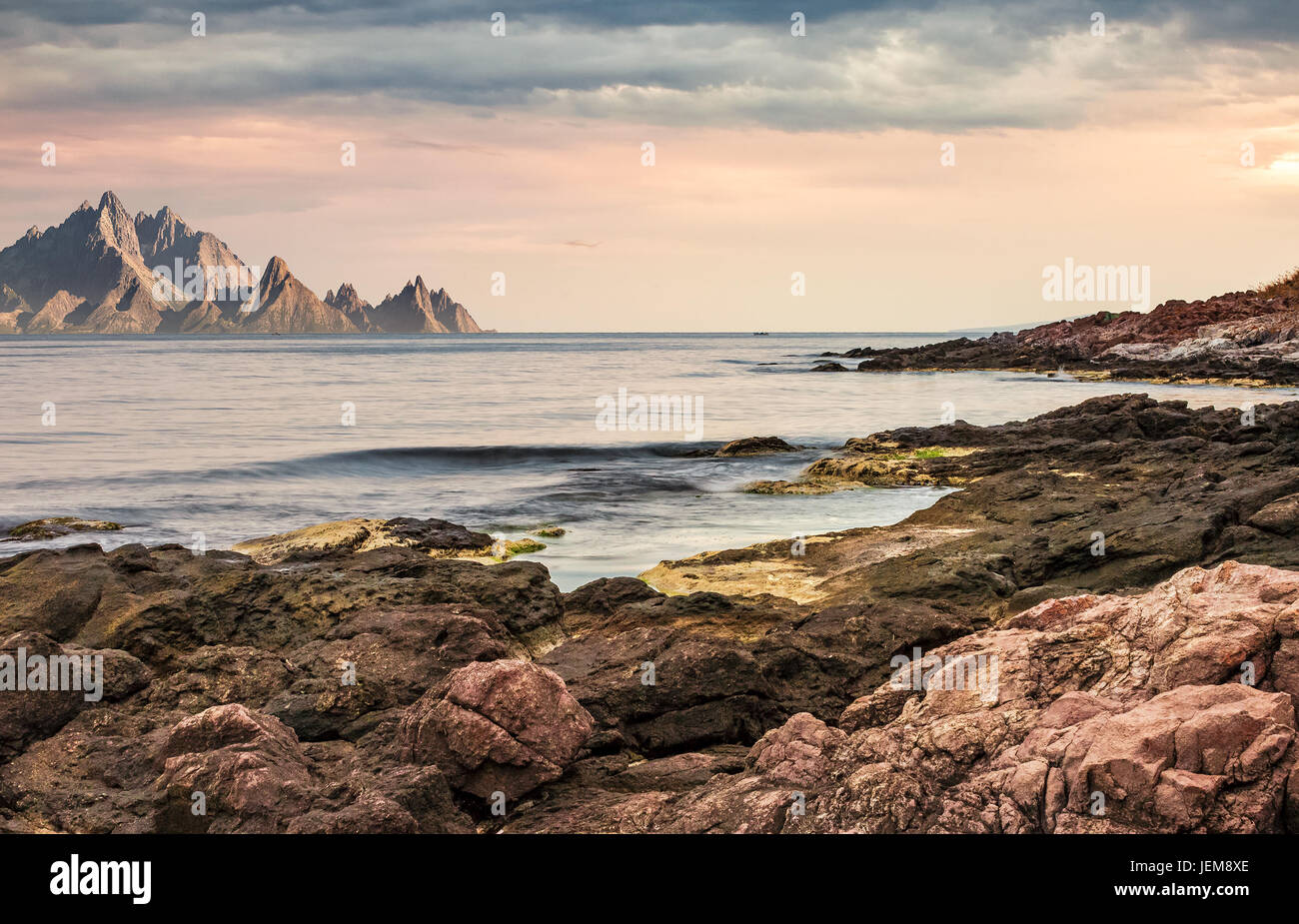 seascape with rocky coast and mountain ridge with high peaks. composite landscape with cloudy sky at menacing sunrise - Stock Image