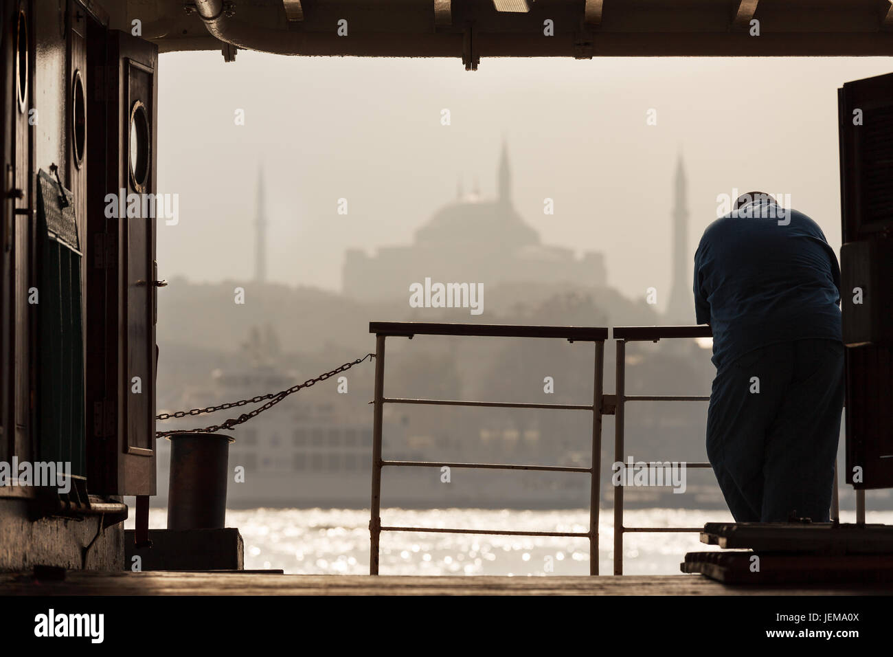 Man standing in the passenger ship and look the beauty of Hagia Sophia in Istanbul and Bosporus. - Stock Image
