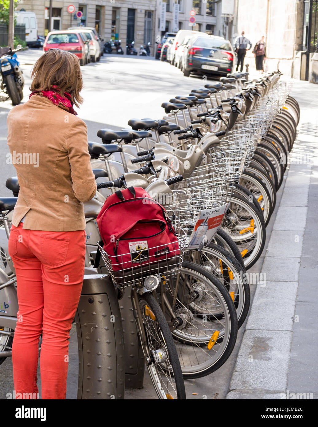 Worman returning a Shared bike in Paris: A young woman returns a Paris sharing bicycle to a long rack of bikes on - Stock Image