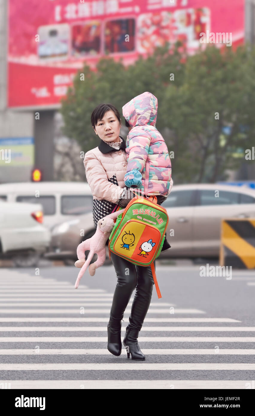 Young Chinese mother carry her child. Driven by fears that an aging population can affect its future economy China - Stock Image