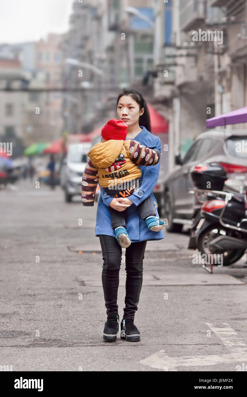 Young Chinese mother carry her child. Driven by fears that an aging population can affect the future economy China - Stock Image