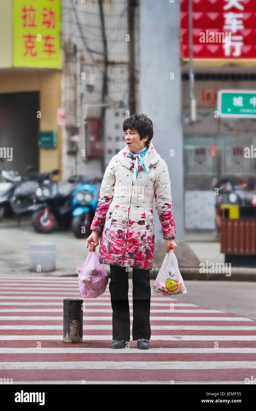 Woman on zebra with groceries. Economic disparity between urban China and rural areas is among the world's largest, forms economic-cultural-social gap Stock Photo