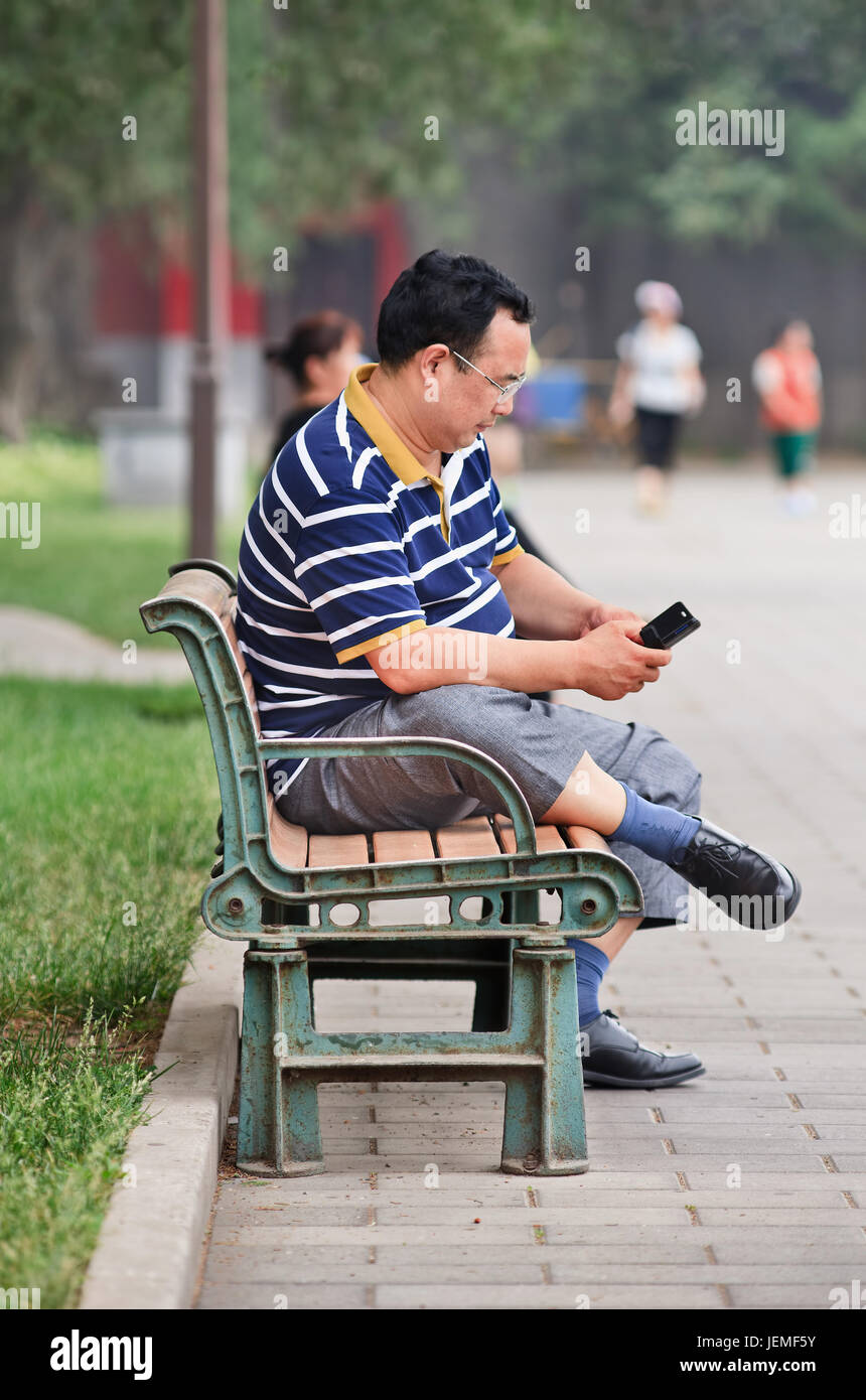 Middle aged overweight Chinese in a park. Obesity in China is a major health concern,  with overall rates of obesity - Stock Image