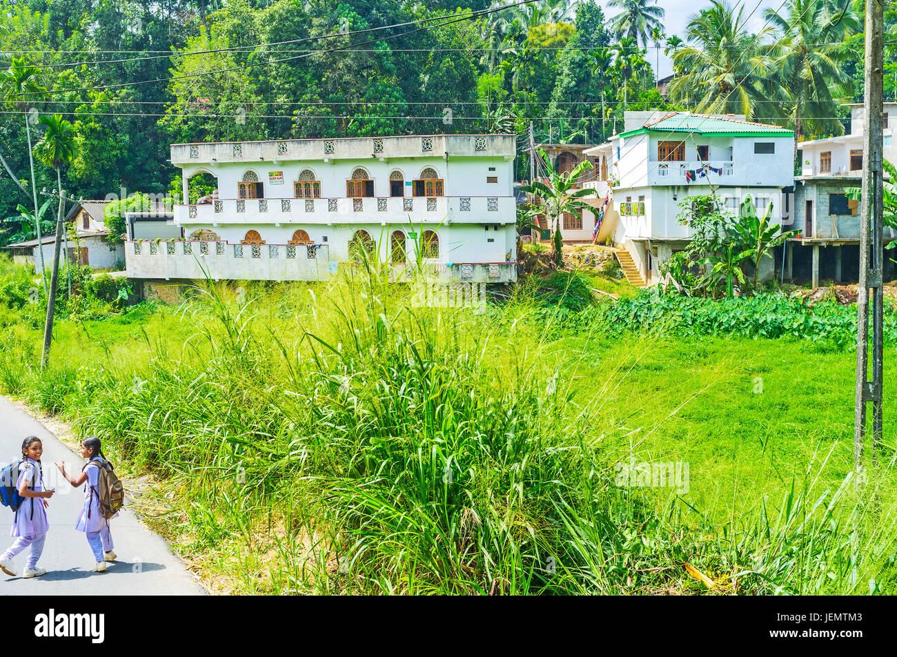 HANDESSA, SRI LANKA - NOVEMBER 29, 2016: The schoolgirls play in the village street on the way home, along the farm - Stock Image