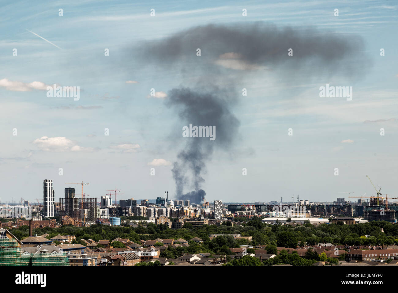 London, UK. 26th June, 2017. Black smoke rises from a large fire in a car storage yard on Ferry Lane, Rainham, East Stock Photo