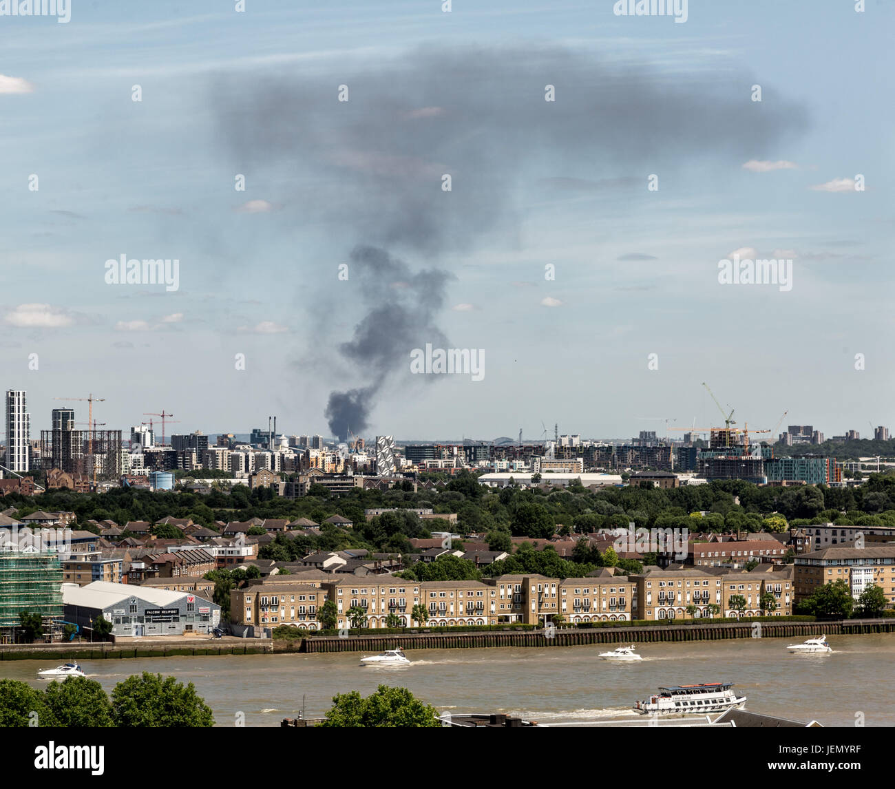London, UK. 26th June, 2017. Black smoke rises from a large fire in a car storage yard on Ferry Lane, Rainham, East Stock Photo