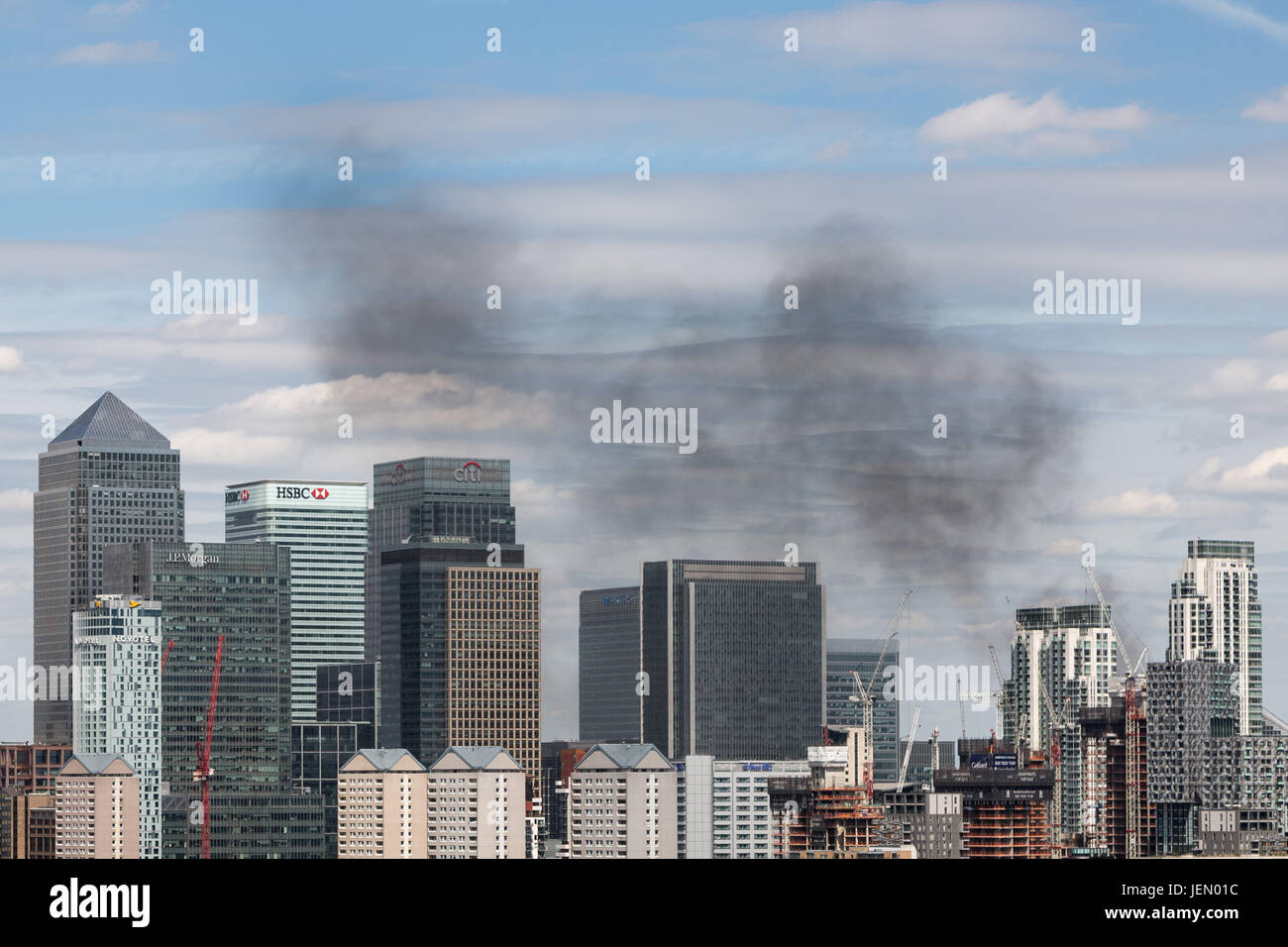 London, UK. 26th June, 2017. Black smoke rises over Canary Wharf buildings from a construction site fire in Wood Stock Photo