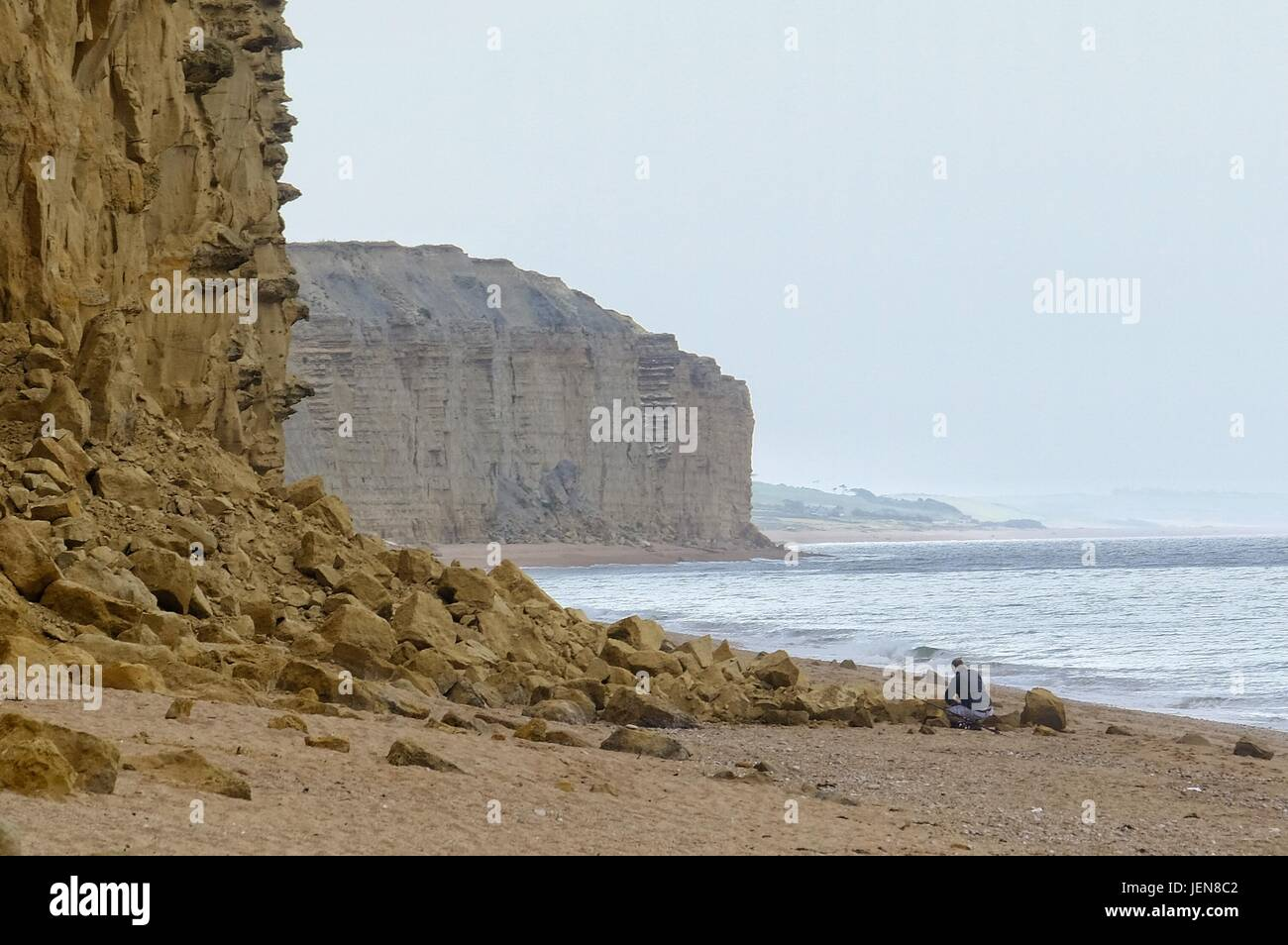 West Bay, Dorset, UK. 27th June, 2017. A fisherman packs away his rods beside a new rock fall on West Bay's - Stock Image