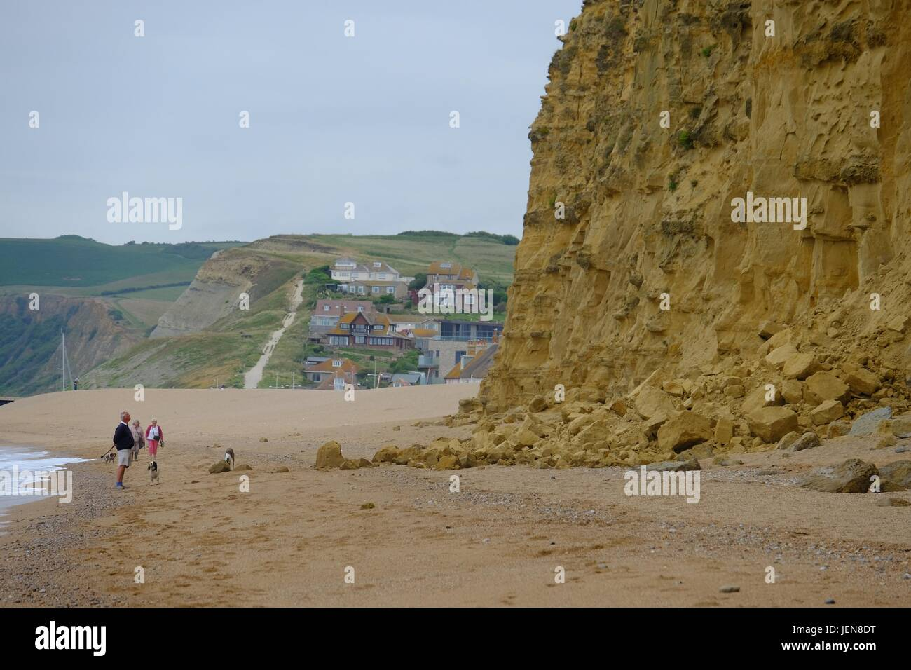 West Bay, Dorset, UK. 27th June, 2017. Walkers skirt the shore to put as much distance as possible between themselves - Stock Image