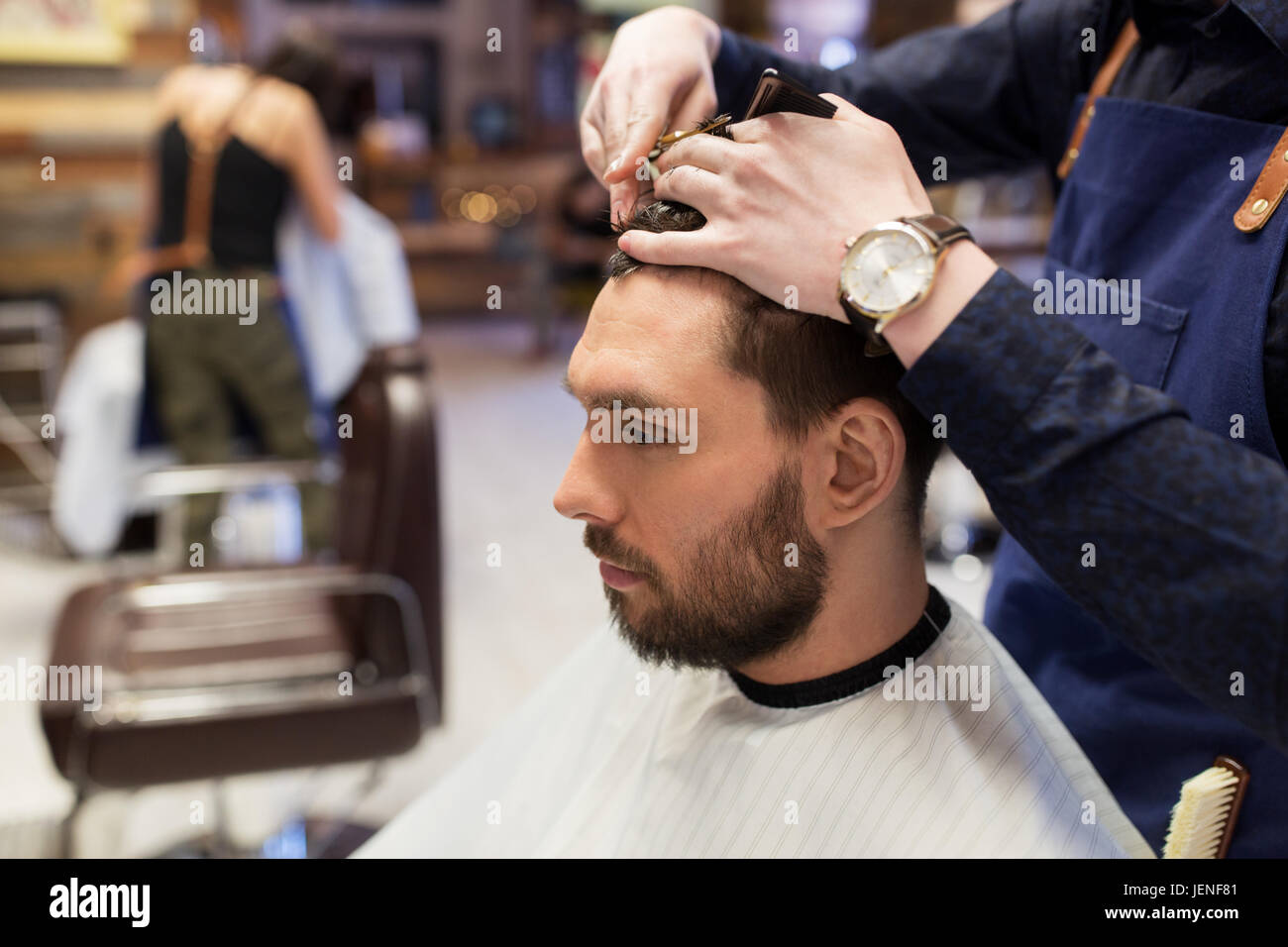 man and barber cutting hair at barbershop - Stock Image