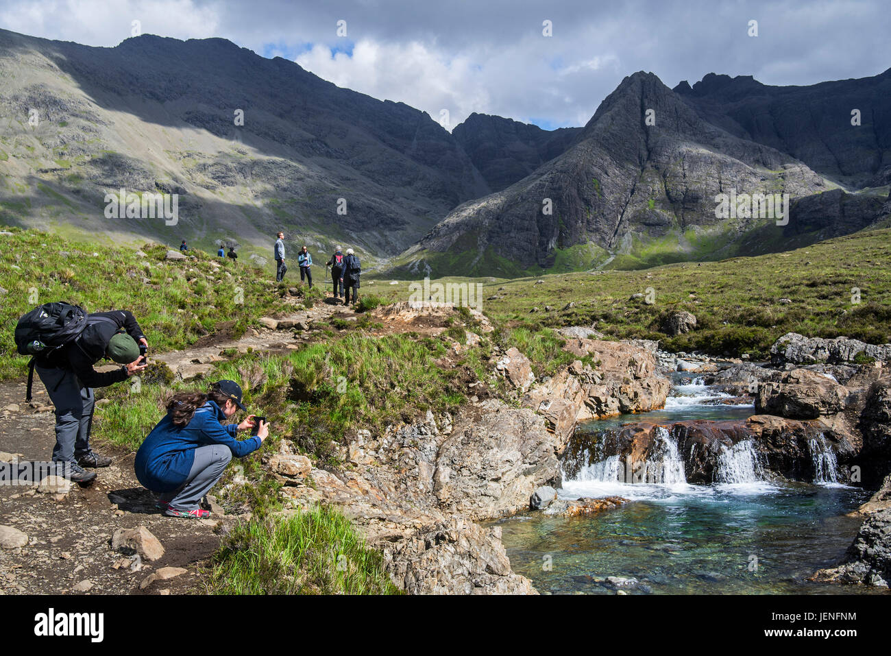 Walkers taking pictures of the Fairy Pools, succession of waterfalls in Glen Brittle on the Isle of Skye, Scottish - Stock Image