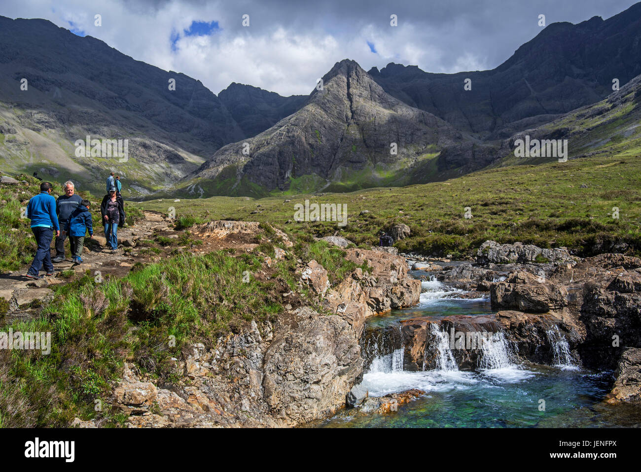 Black Cuillin and tourists visiting the Fairy Pools, succession of waterfalls in Glen Brittle on the Isle of Skye, - Stock Image