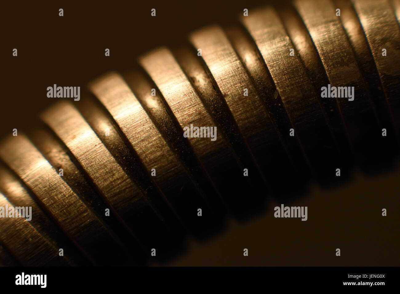 Abstract background with a metal spring emerging from the darkness. - Stock Image