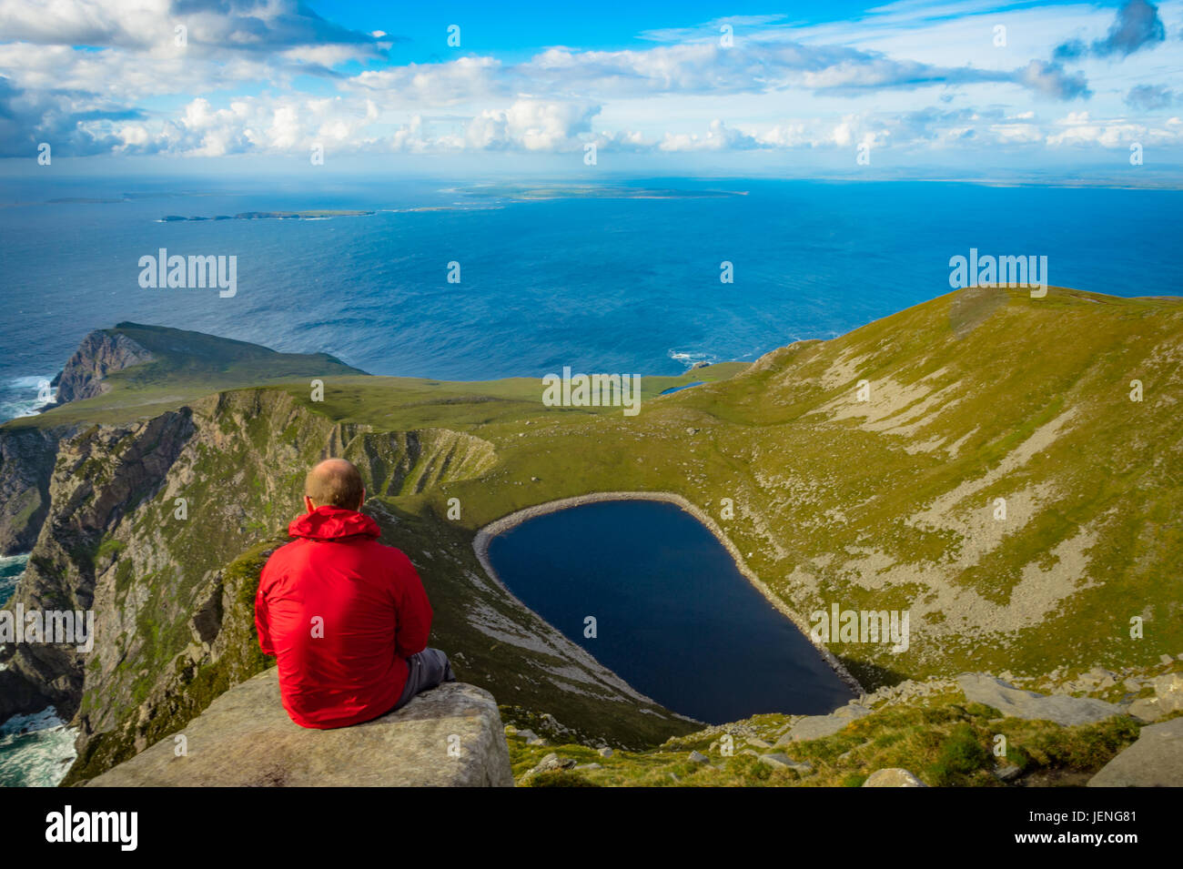 Man looking at a lake in a hill on Achill island, Co. Mayo. - Stock Image