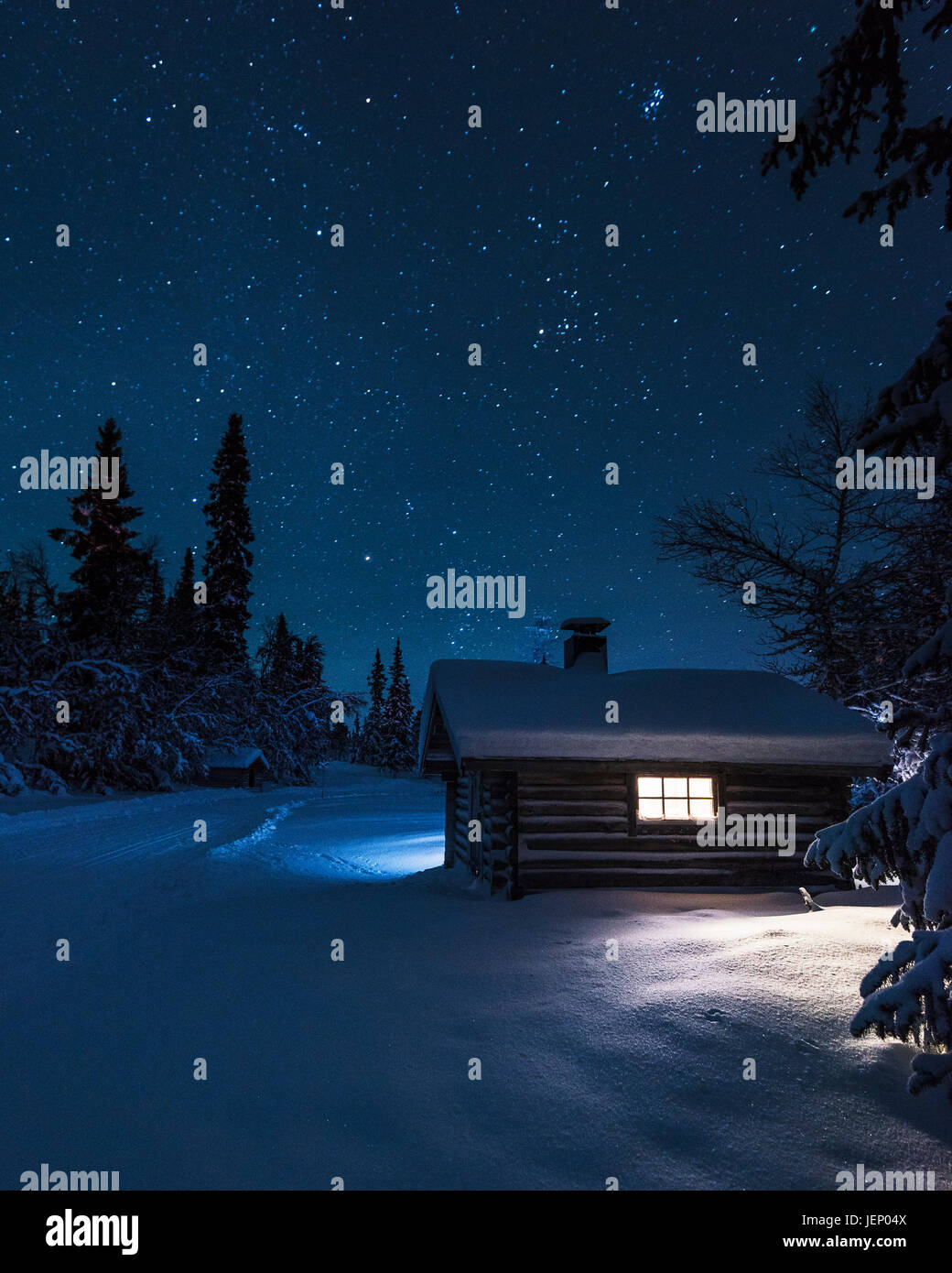 Illuminated log house at night - Stock Image