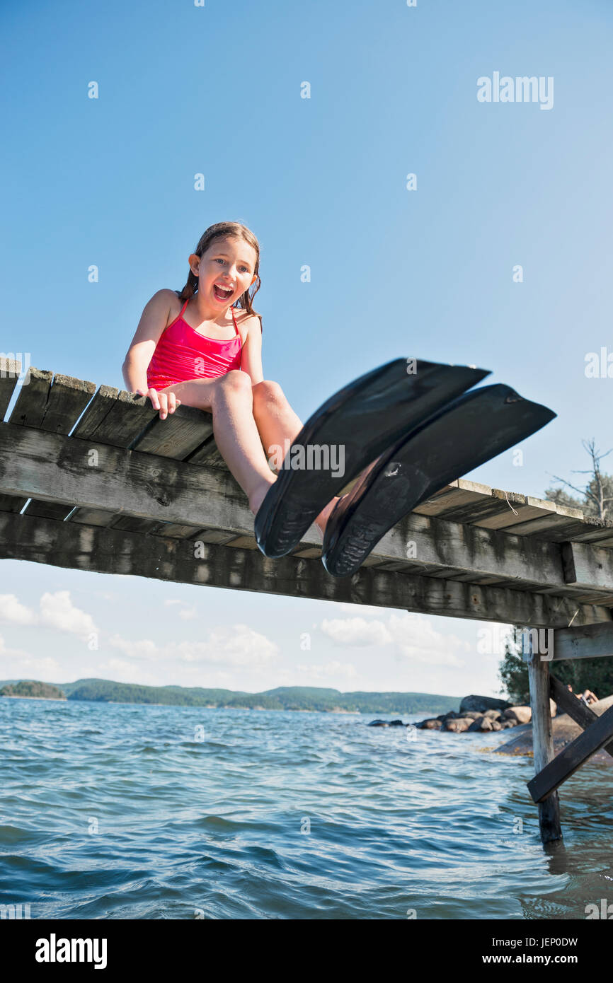 Happy girl wearing flippers on jetty Stock Photo