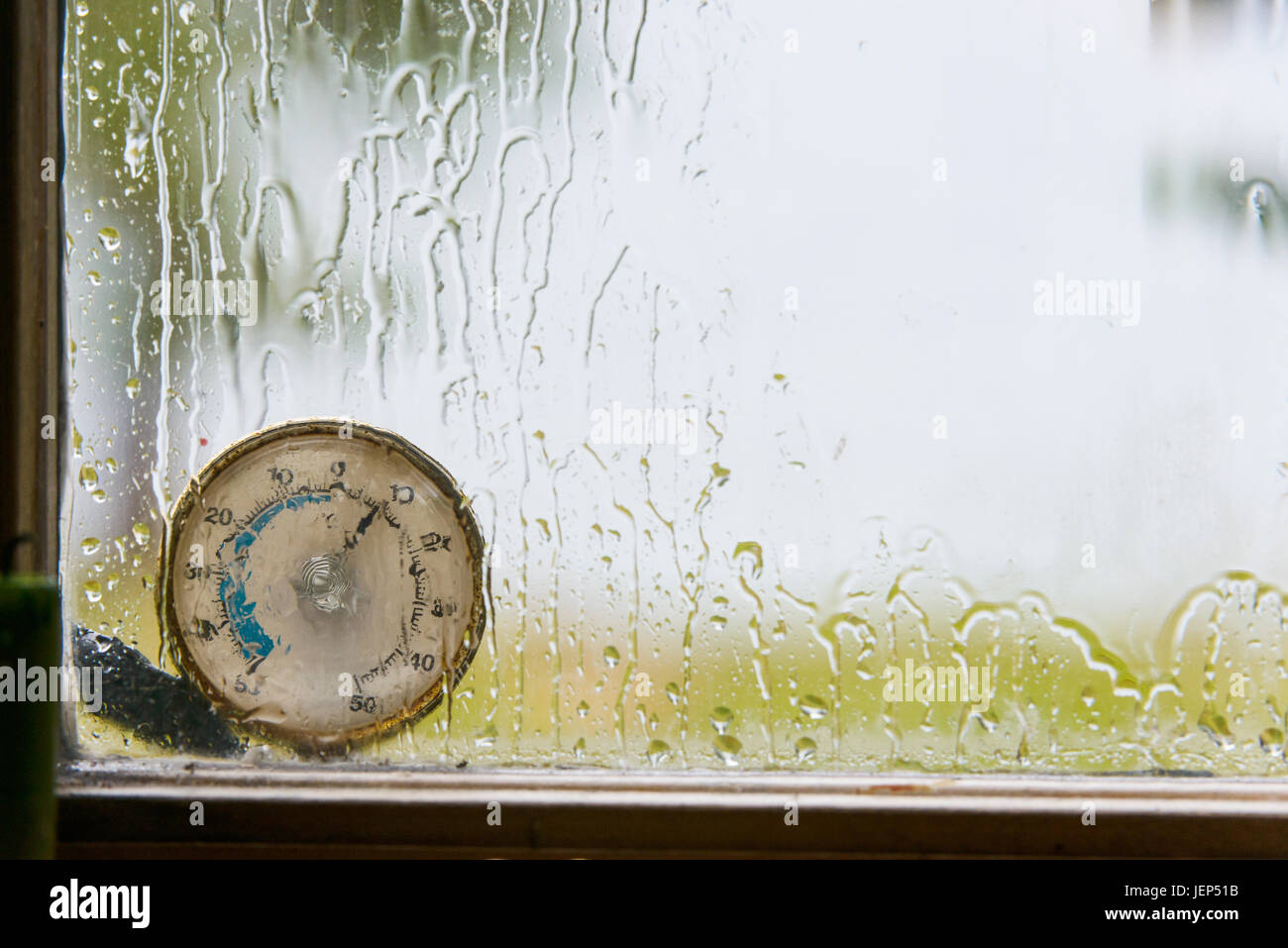 Thermometer behind window - Stock Image