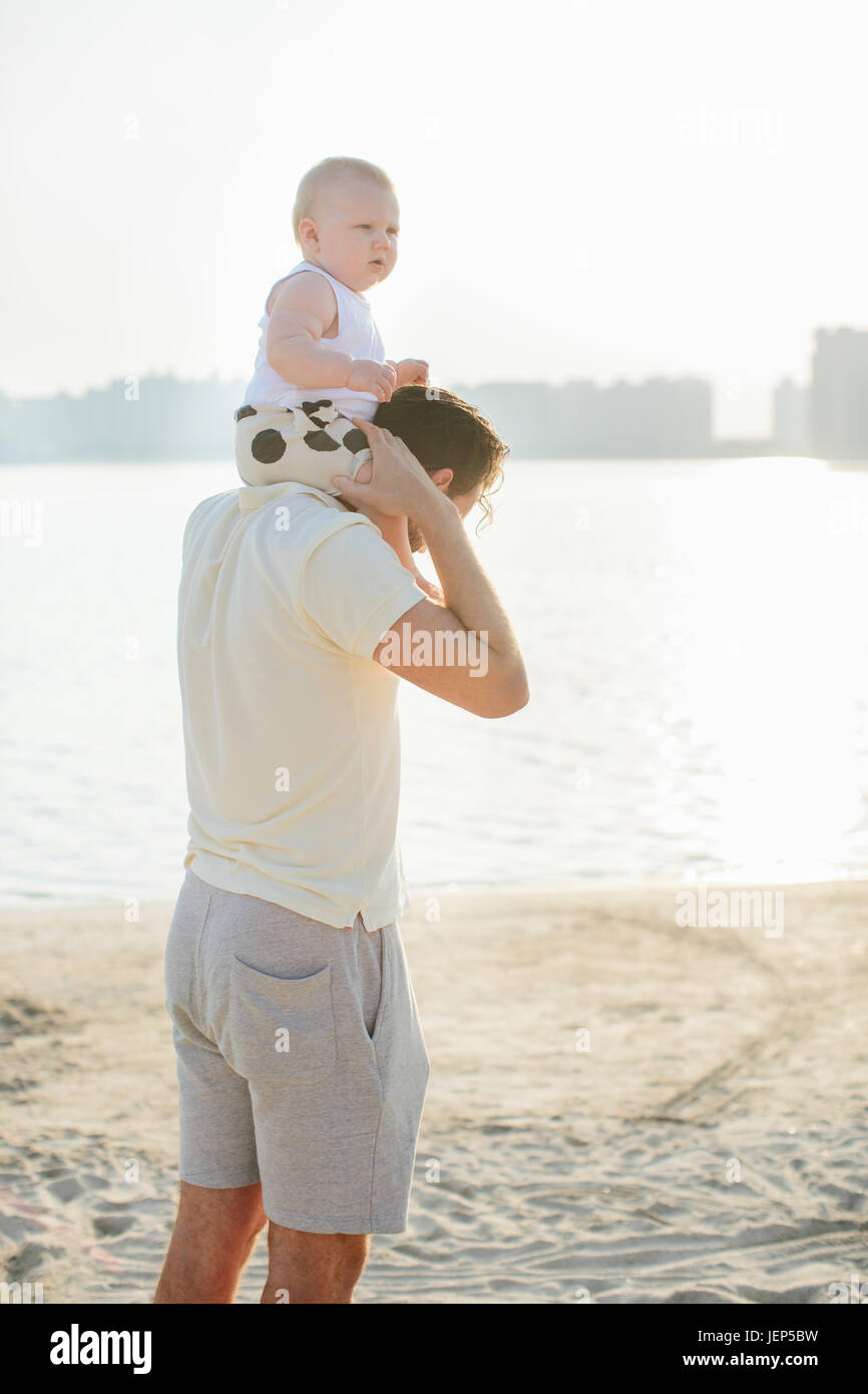 father carrying baby on shoulders at beach Stock Photo