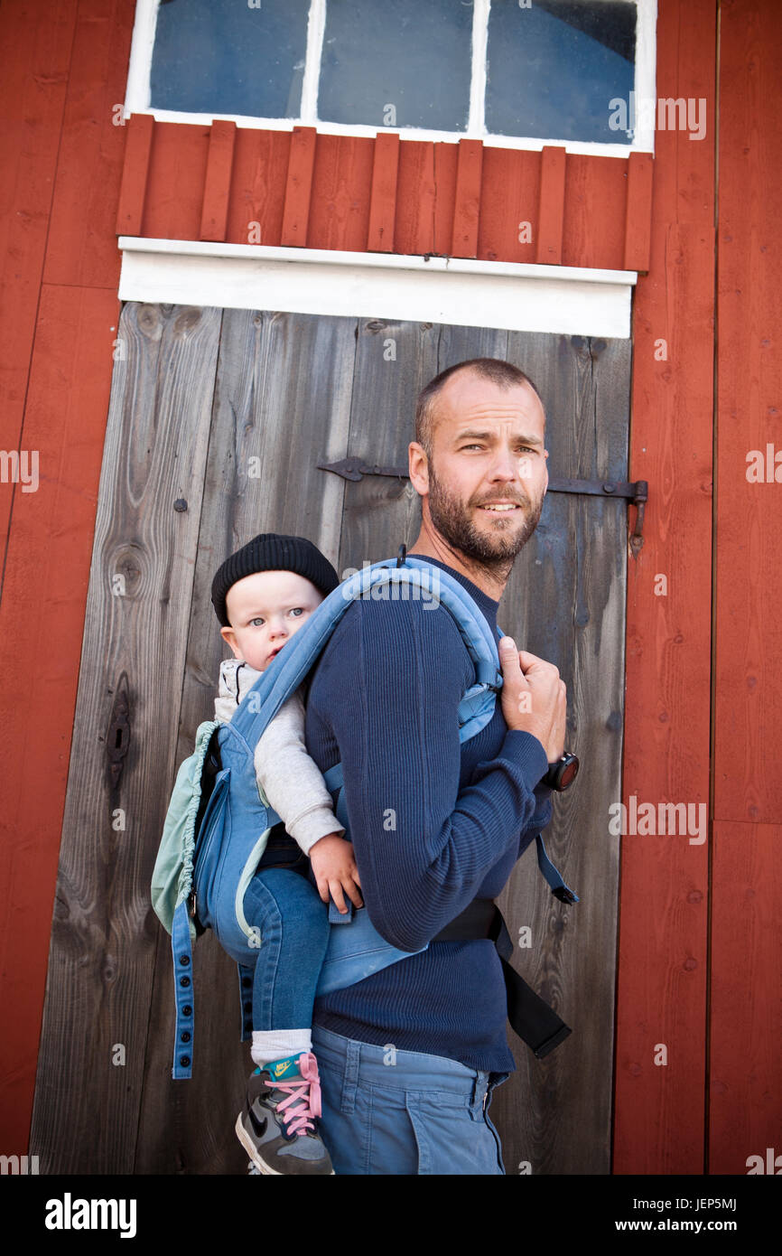 Father carrying his baby son in baby carrier - Stock Image