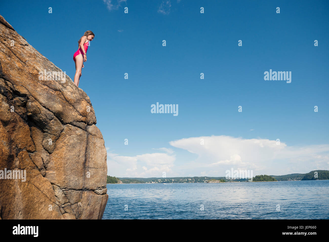 Girl standing on cliff Stock Photo