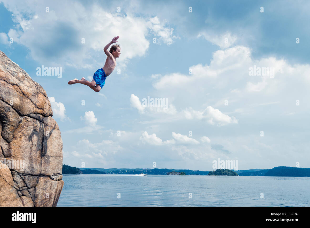Boy jumping into sea Stock Photo