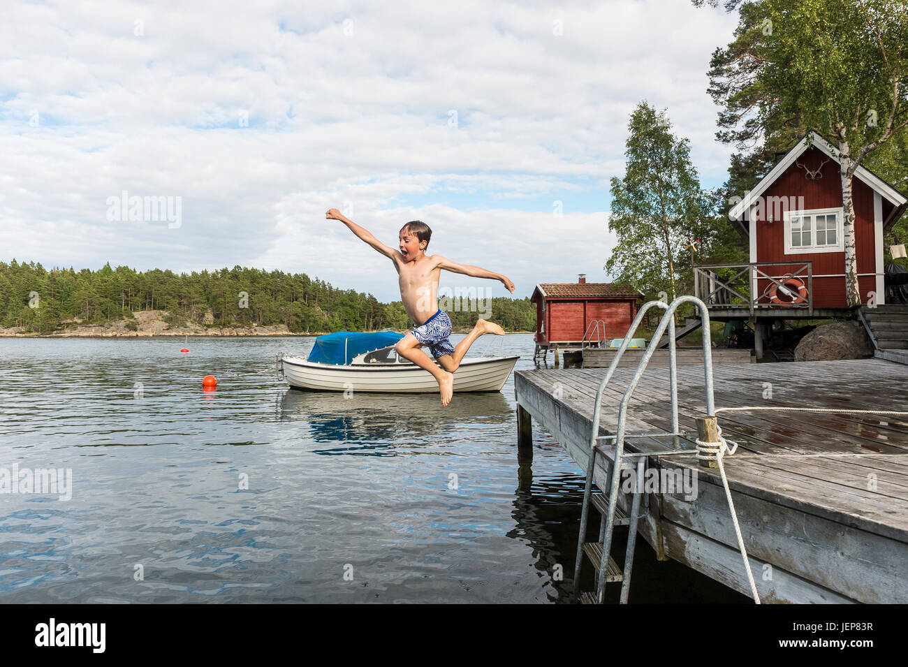 Boy jumping from jetty Stock Photo
