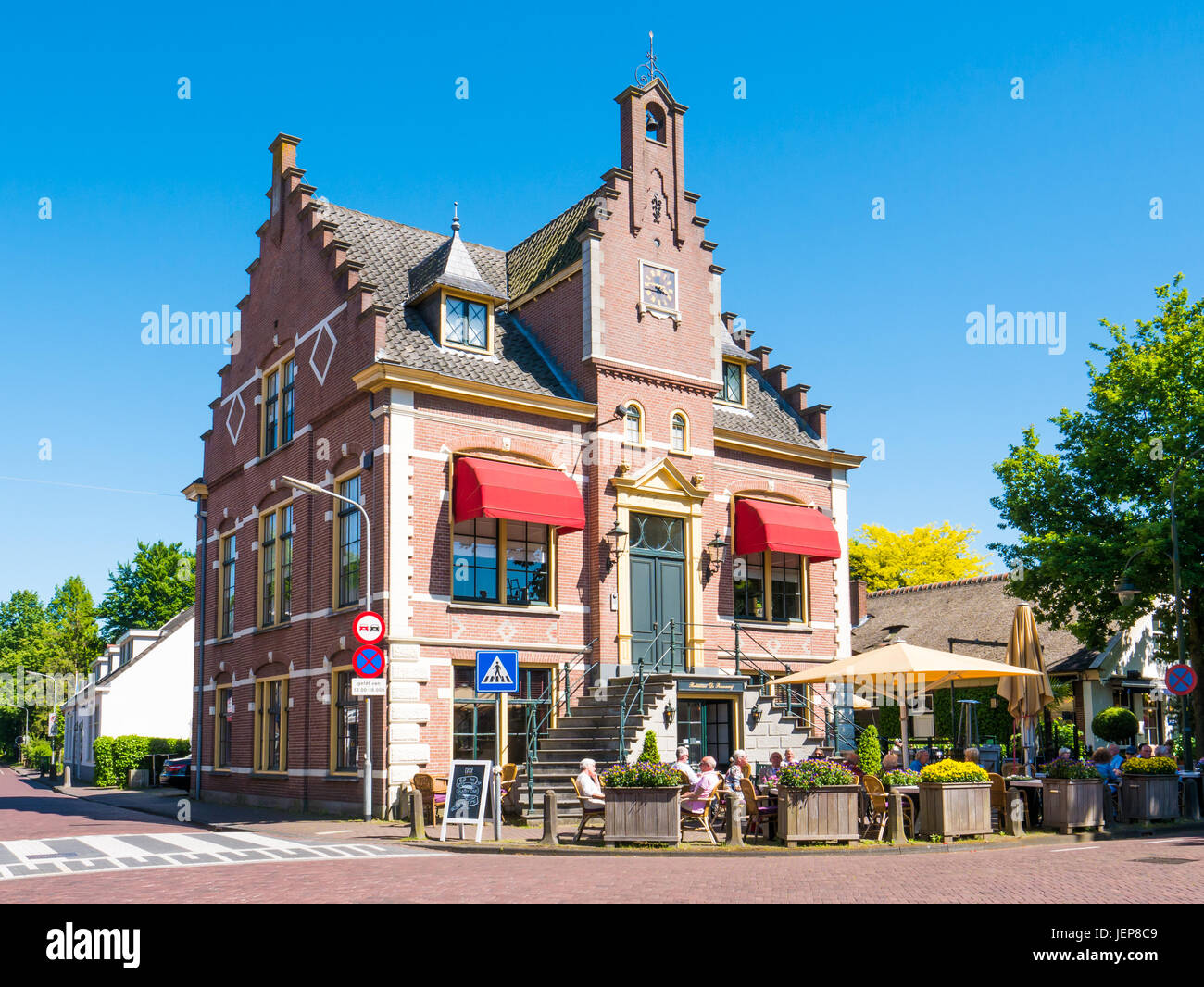 People relaxing on outdoor terrace of restaurant in former town hall of Laren, North Holland, Netherlands - Stock Image
