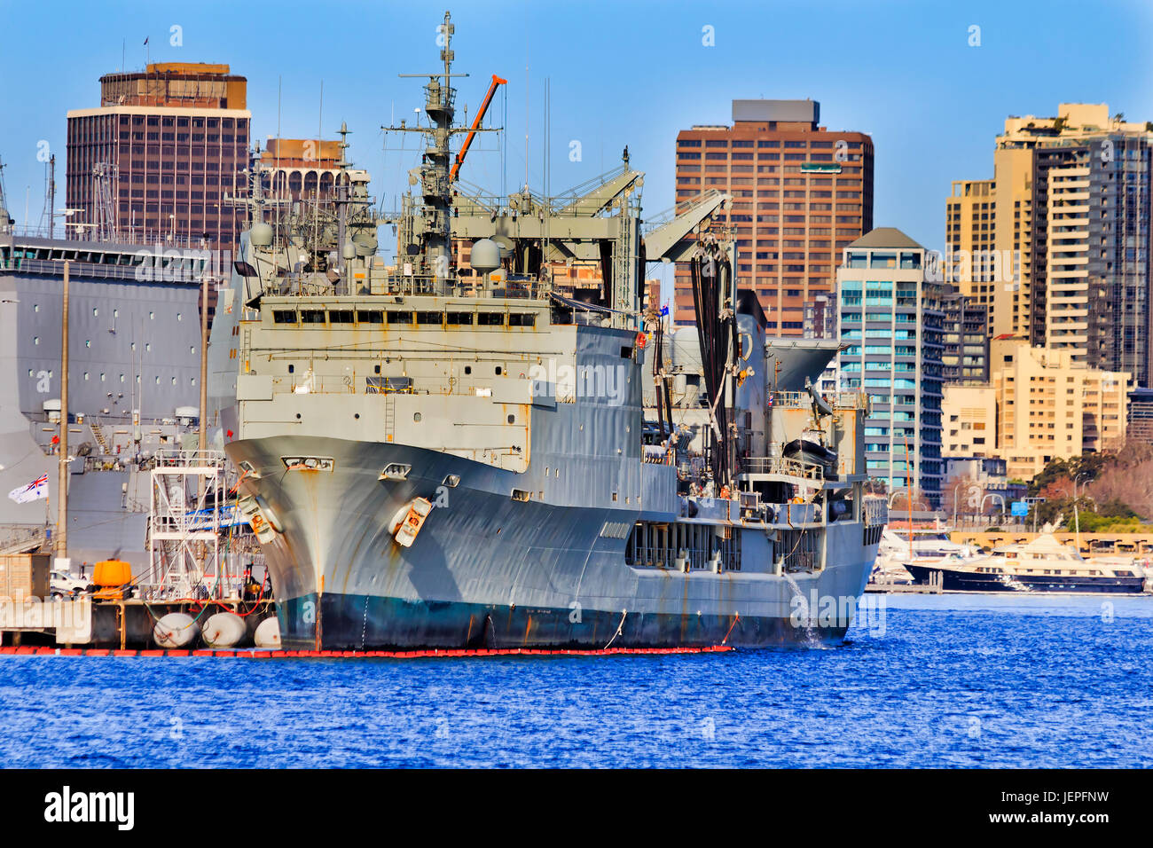 Front of Her Majesty Australian ship at military navy base in Sydney cove on a sunny day against residential high - Stock Image