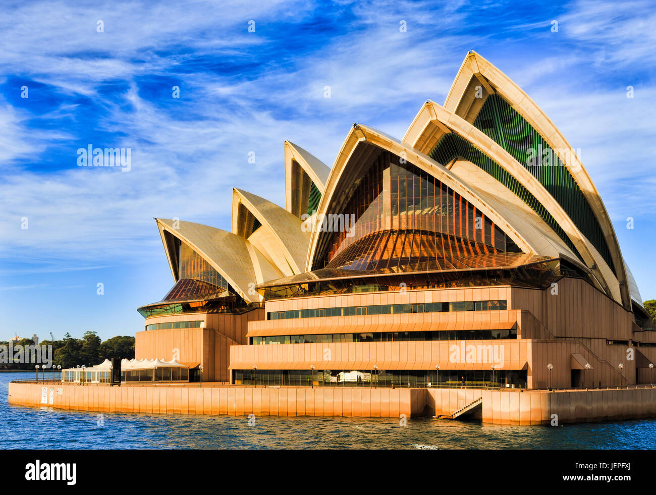 Sydney, AUstralia - 24 June 2017: Sydney Opera house on a bright sunny day rising from Sydney harbour waters in Stock Photo