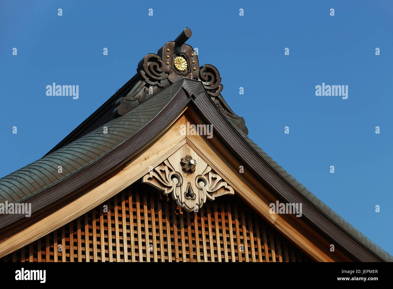 Peak end of an ornate roof with wooden carvings in the Yasukuni Shrine complex in Tokyo, Japan. Warm brown wood - Stock Image