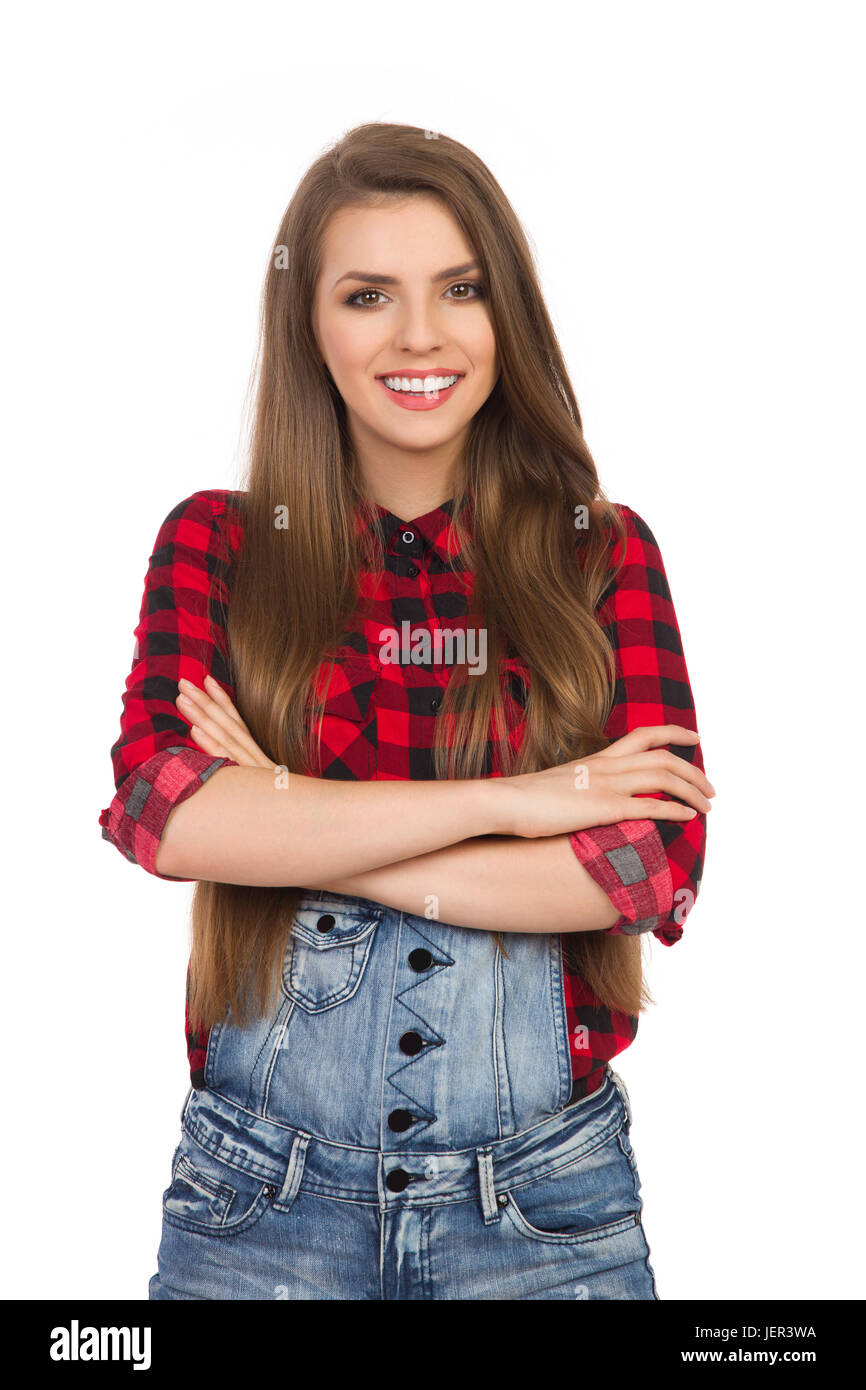 d0837ee7afcd42 Woman in red lumberjack shirt and jeans dungarees posing with arms crossed.  Waist up studio