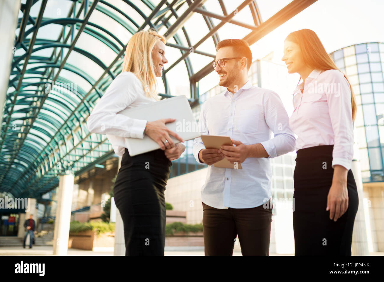 Picture of young attractive business partners standing outdoor - Stock Image