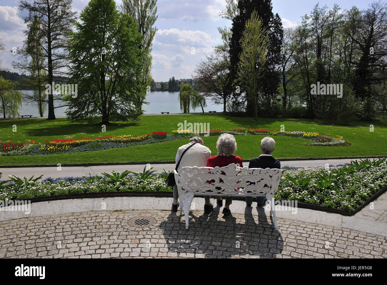 Island Mainau in Lake of Constance, three older people rest on a bank in the garden of the island Mainau, Insel - Stock Image